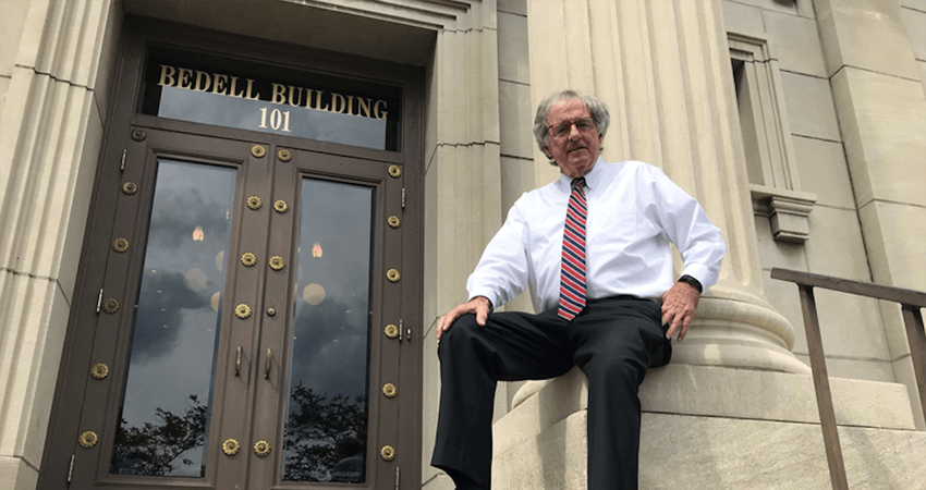 Hank Coxe sits against a podium outside of the Bedell Firm building