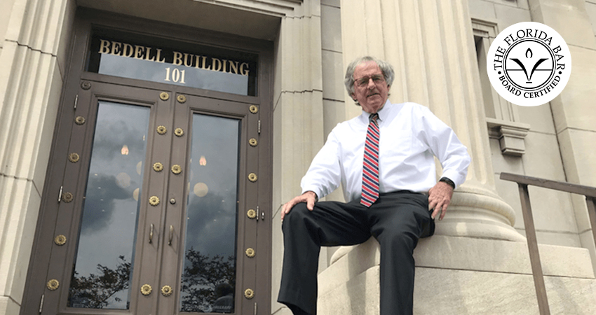 Hank Coxe sits against a podium outside of the Bedell Firm's building
