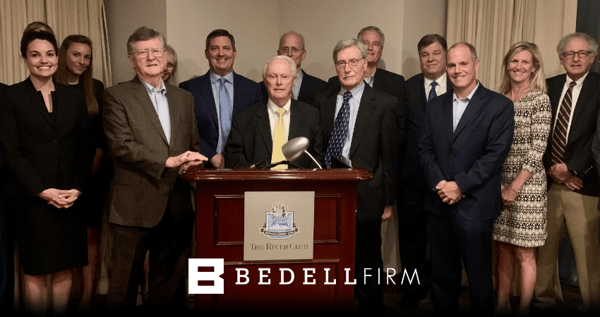 Bedell firm attorneys stand with Charles P. Pillans, III in front of a podium. A white Bedell Firm logo is at the bottom